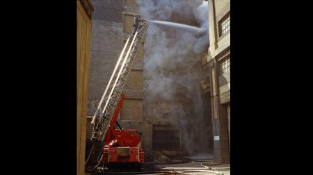 A firefighter faces thick smoke while tackling the fire from the top of a turntable ladder